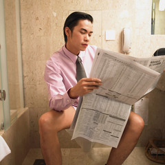 Businessman reading newspaper while sitting on toilet