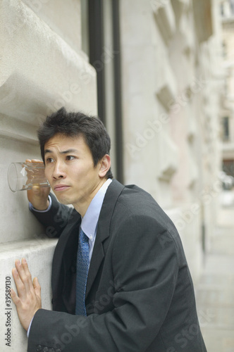 Businessman listening through glass on wall