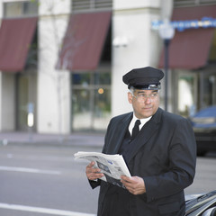 Chauffeur reading newspaper