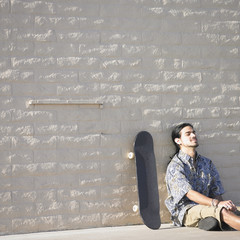 Man sitting against wall with skateboard
