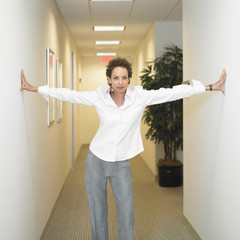 Businesswoman with arms outstretched to walls