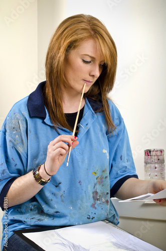 Attractive young female artist in blue clothing, painting