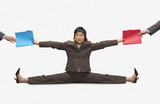 Businesswoman stretching to give folders to colleagues