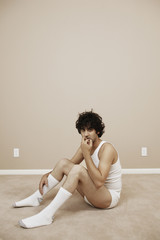 Forlorn young man sitting in his underwear