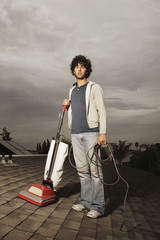Young man vacuuming on roof