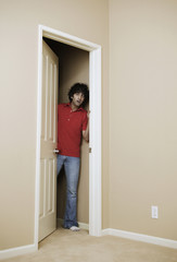Young man peeking through the door