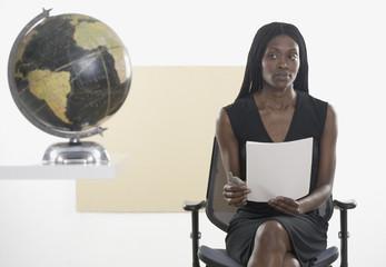 Businesswoman examining a globe