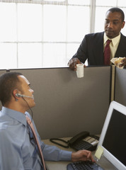 Businessmen talking over cubicle wall