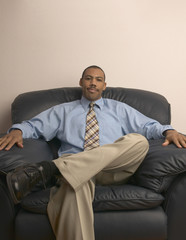 Businessman relaxing in leather armchair