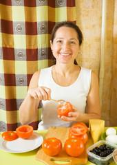 Mature woman making stuffed tomato