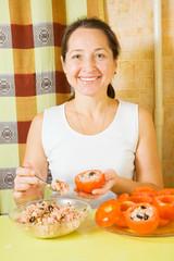 Female cook stuffing tomato