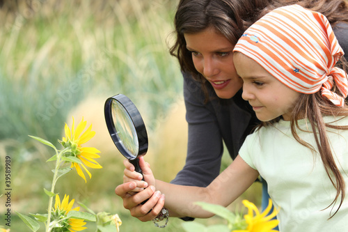 Mother and daughter looking at a flower with a magnifying glass