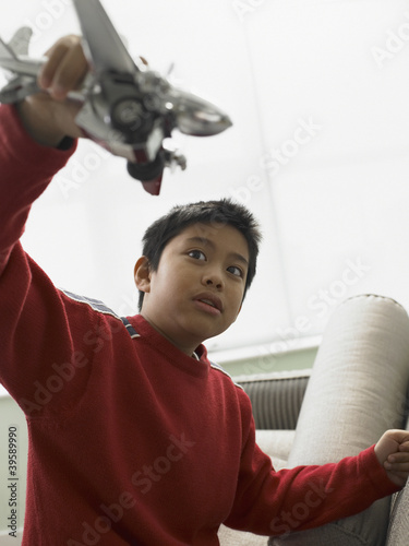 Young boy playing with a model plane