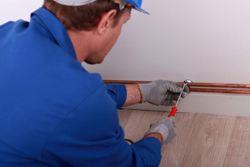 Plumber securing pipe to wall