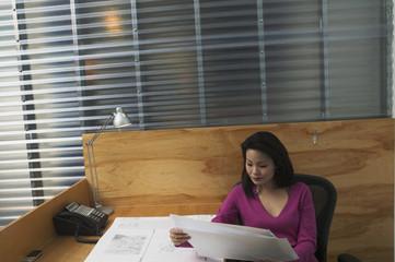 Businesswoman examining blueprints