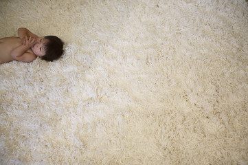 Bare chested baby lying on thick rug