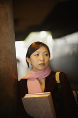 Asian woman carrying books