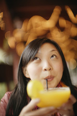 Asian woman drinking cocktail with straw