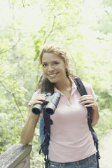 Young female hiker using binoculars