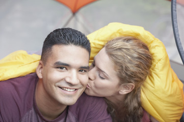 Woman kissing man in a tent