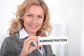 Smart woman holding a sign entitled 'ADMINISTRATION'