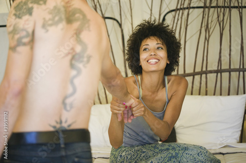 African American woman pulling man onto bed