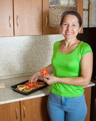 Woman adds tomato on stuffed vegetable marrow