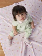 Overhead view of baby girl sitting on floor mat