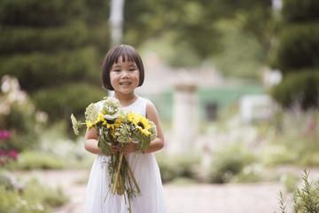 Girl in garden holding flowers