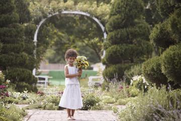 Girl standing in garden holding flowers