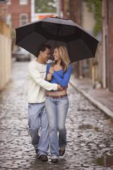 Couple walking together under umbrella