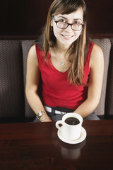 Woman in booth with cup of coffee