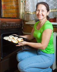 woman roasting stuffed vegetable marrow