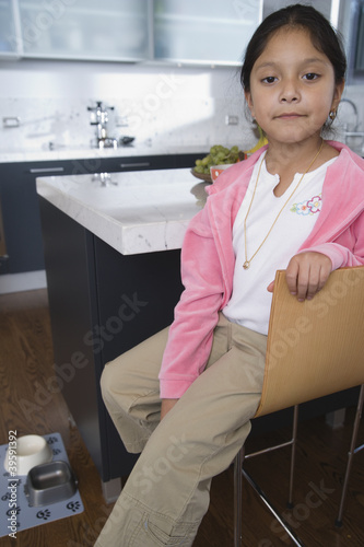 Girl sitting in kitchen at home