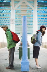 Two young adults waiting for train
