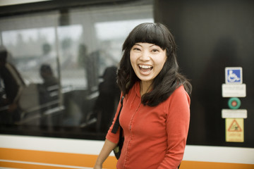 Young woman laughing at metro station