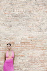 Young woman in front of a brick wall