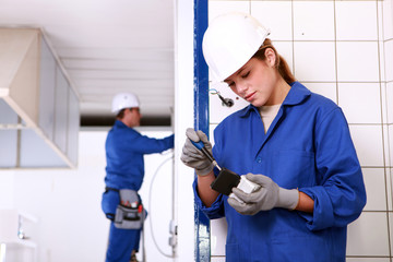 Male and female electricians working together