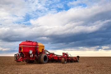 Seeding machine on the empty field at sunset