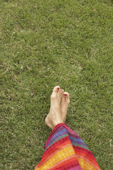 Feet of young woman on grass