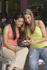 Two young women reviewing digital photos