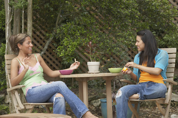 Two young women eating together outside