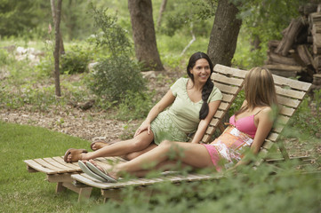 Two young women sitting on lounge chairs
