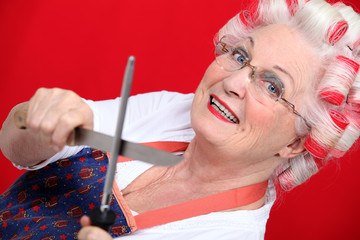 grandmother with haircurlers sharpening knives