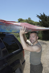 Man lifting kayak onto SUV roof