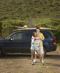Couple standing alongside car on road trip