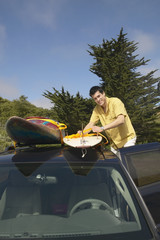 Man tying surfboard to car rack
