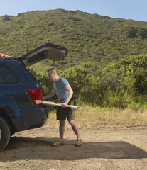 Man packing surfboard into SUV
