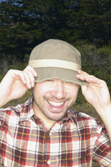 Man pulling hat over his eyes