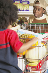Young African American brothers pushing shopping cart